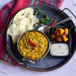 square image of arisi paruppu sadam served in kadai with papad, raita and arbi roast placed on a rustric tray