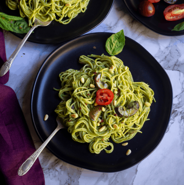 square image of pesto pasta served in black plate with cherry tomato on top