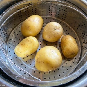 adding potatoes to the steamer rack of Instant Pot