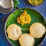 poori served with potato masala in a plate lined with banana leaf and coffee on the side