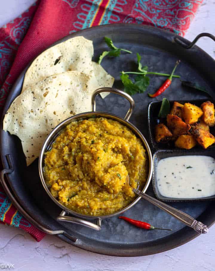 samai paruppu sadam in a kadai bowl with spoon inside with side dishes