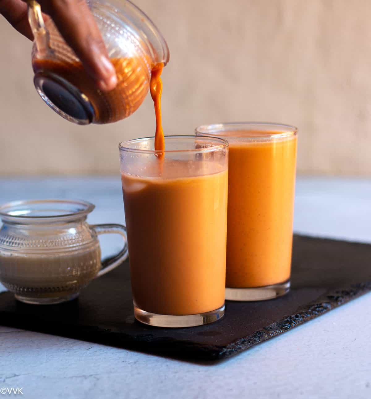 pouring shot of thai iced tea into a tall glass placed on slate board