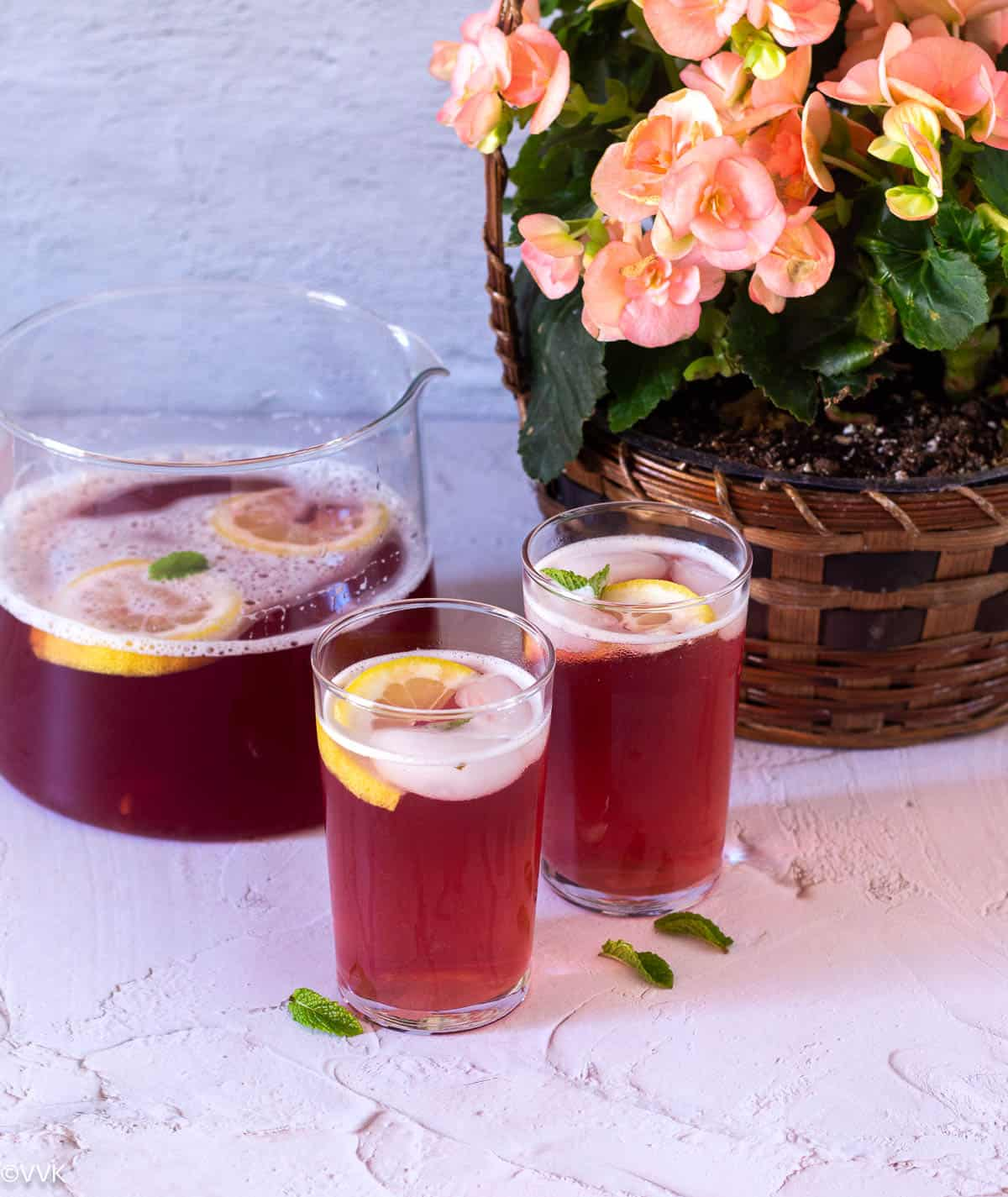 instant pot raspberry iced tea in two glasses with pitcher on the back