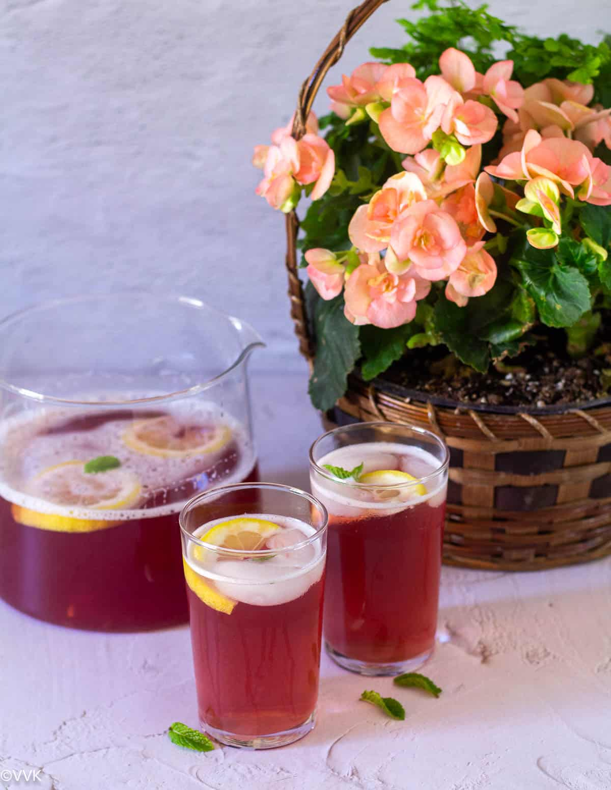 instant pot raspberry iced tea in two glasses with pitcher on the back and a flower basket on the back