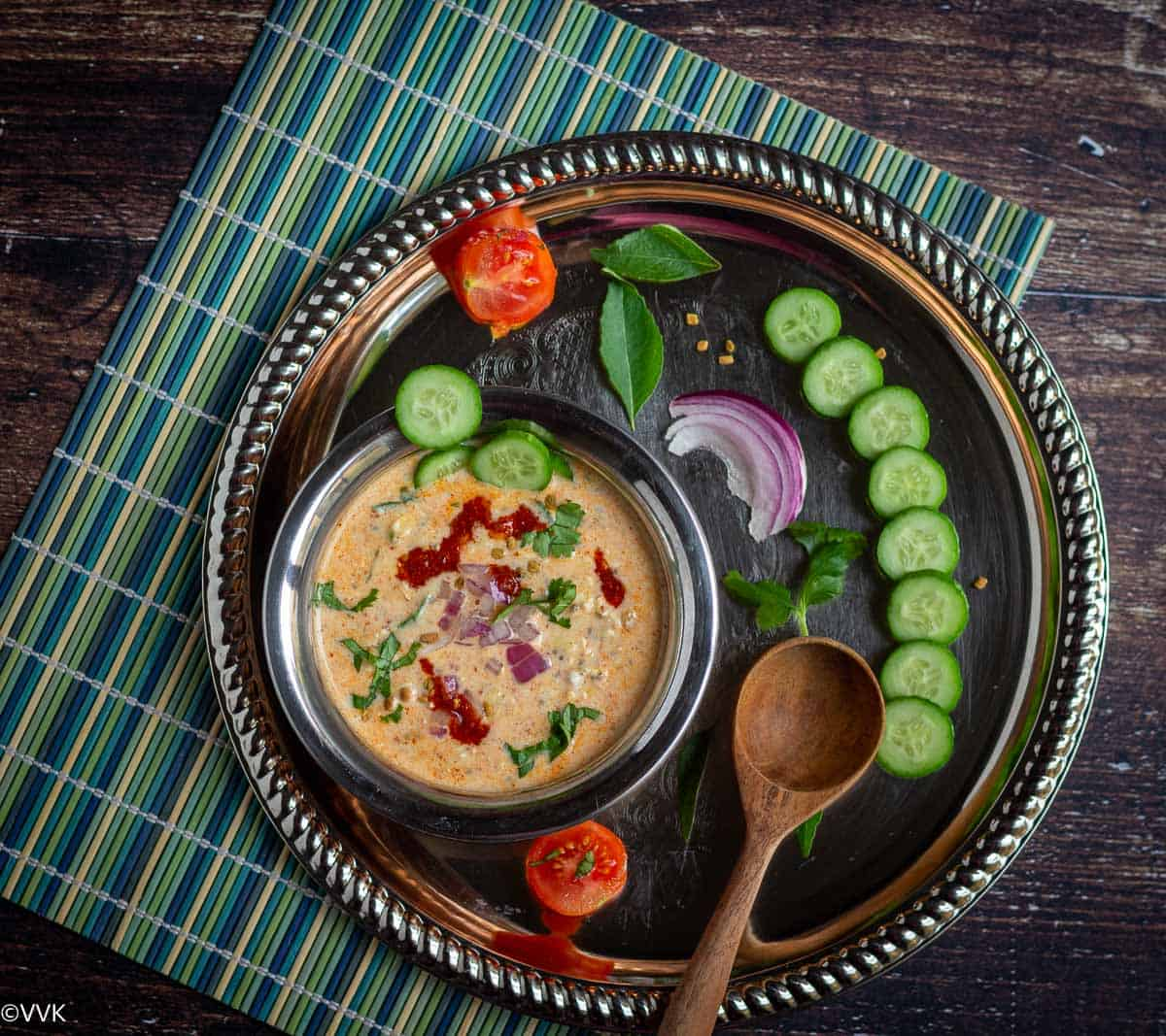 overnihgt pickle oats served in kadai bowl placed on a silver plate with cut cucumbers, tomato, onion topped with onions