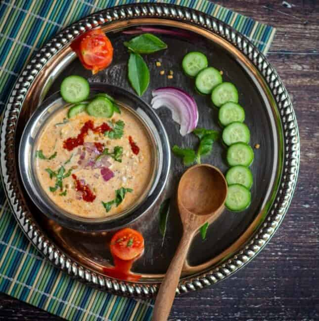 overnight savory oats served in kadai bowl with fresh cucumbers on the side