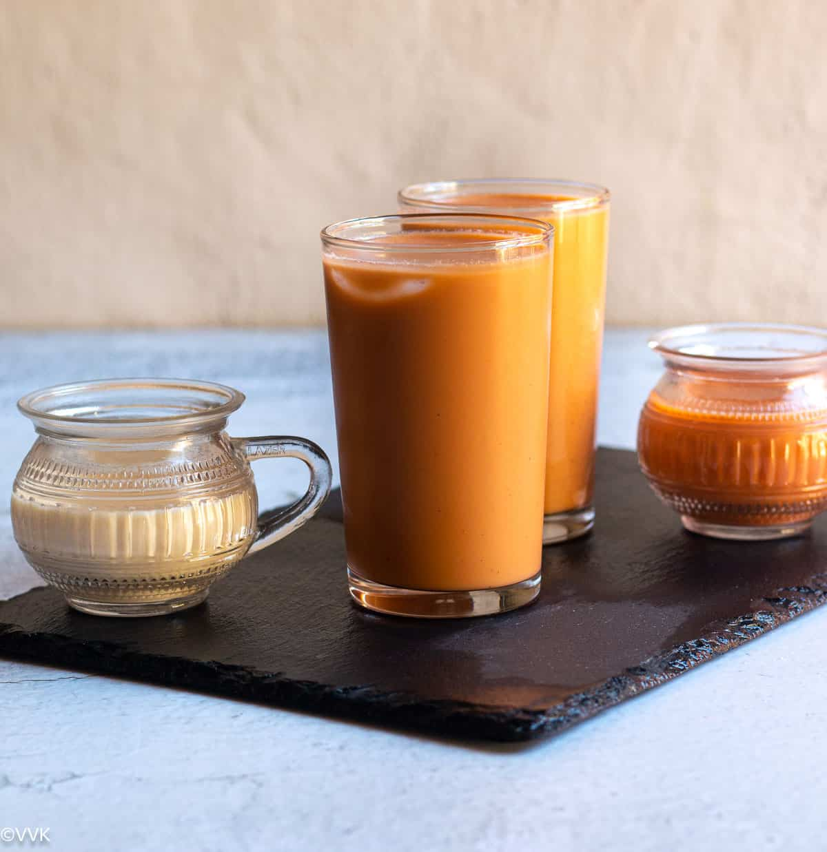 thai iced tea served on two tall glasses placed on slate board with milk and brewed tea on the side