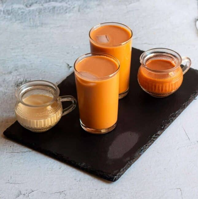 square image of thai tea served in glassed placed on a black slate board