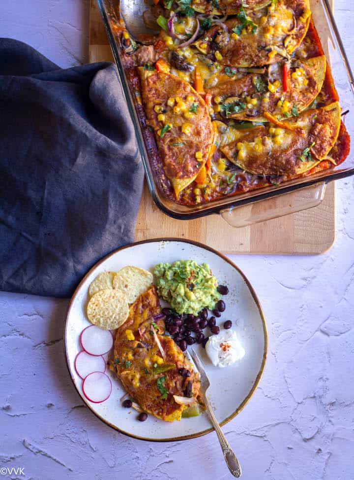 enchiladas baked in glassware and served on a white plate with sides