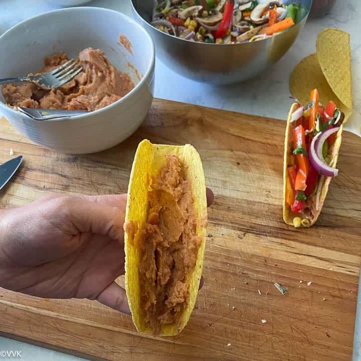 adding refried beans to the taco shells