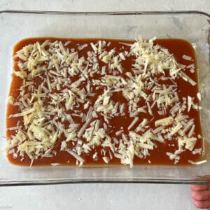 adding the bottom layer of cheese and sauce