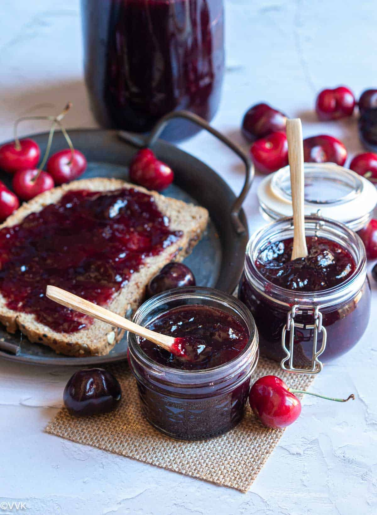 cherry jam stored in two bottles placed on burlap cloth and on the side bread is smeared with cherry jam