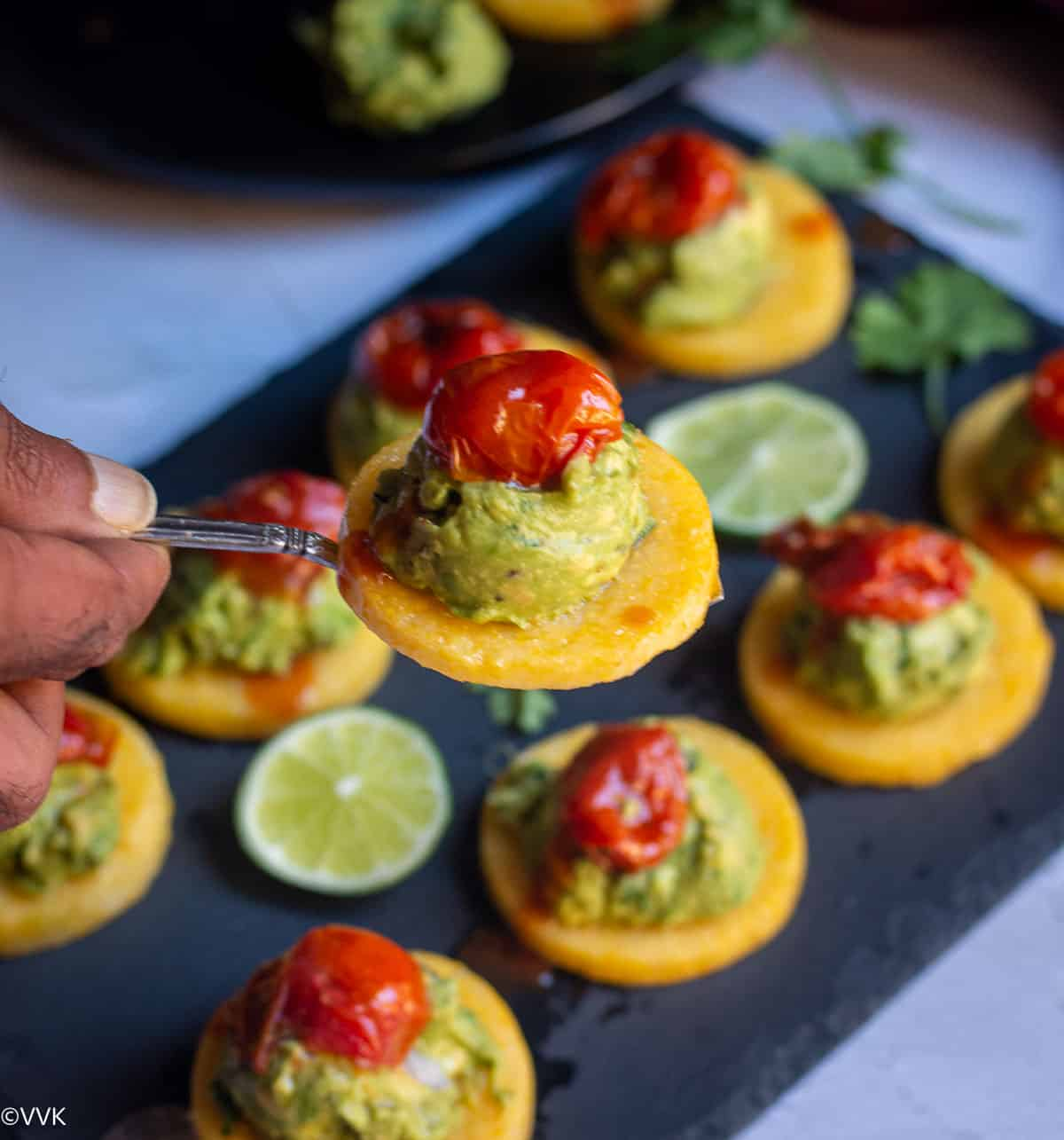 handheld closeup shot of baked polenta topped with guacamole and tomatoes