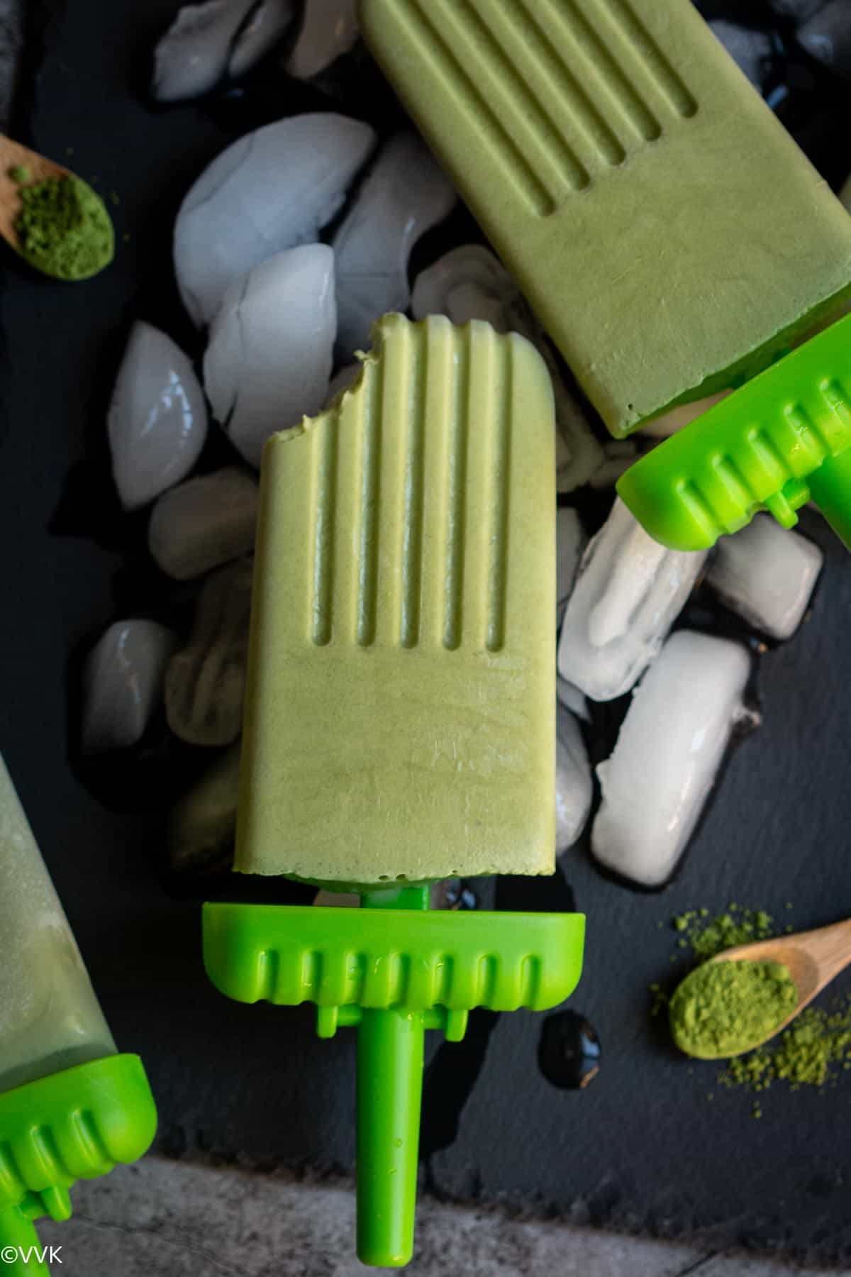 two green tea matcha popsicles on black slate board with ice cubes