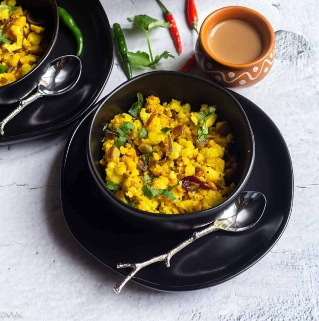 square image of idli upma served in a black bowl with tea on the side
