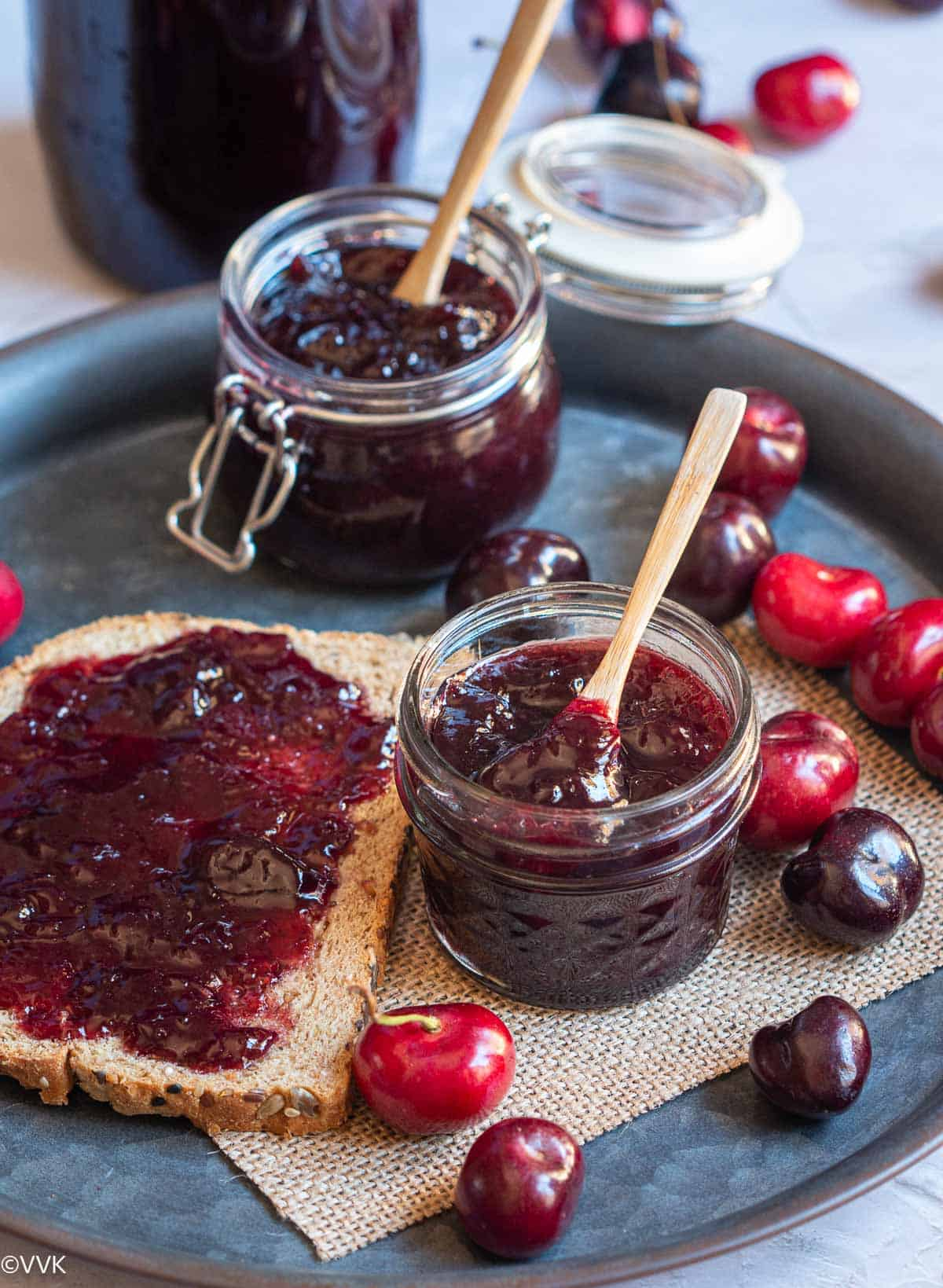 cherry jam in two bottles with bread smeared with the jam placed on a iron tray