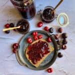 overhead shot of bread smeared with cherry jam with jam bottles and fresh cherries on the side
