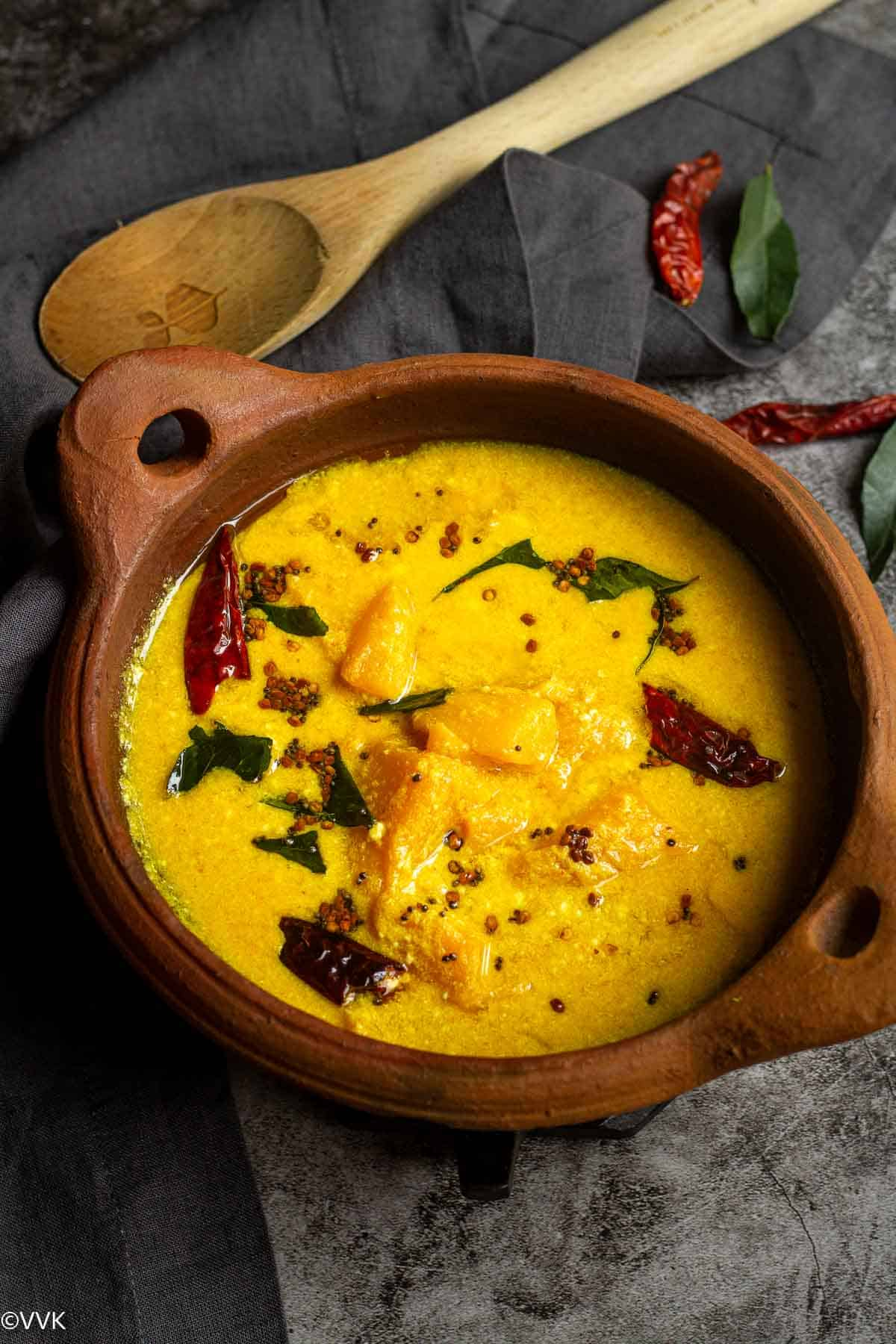 kerala style mambazha pulissery served in clay pot with a ladle on the side and few dried red chilies and curry leaves on the side