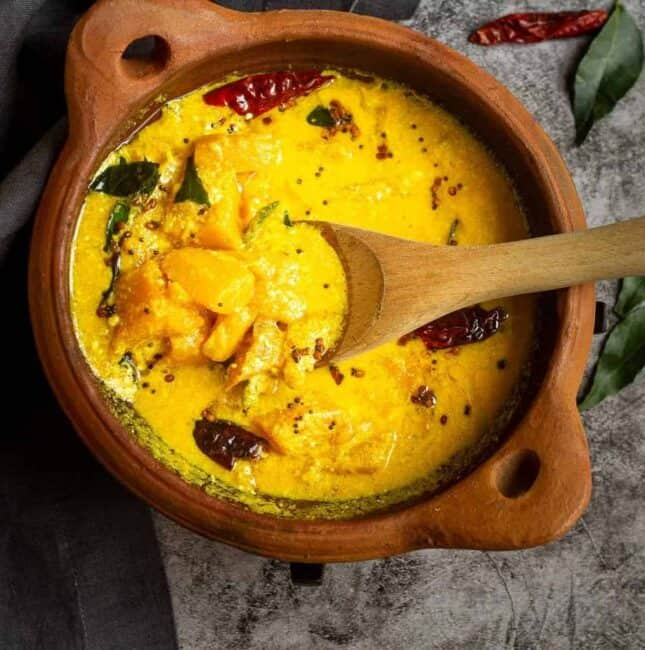 square image of mango curry served in clay pot