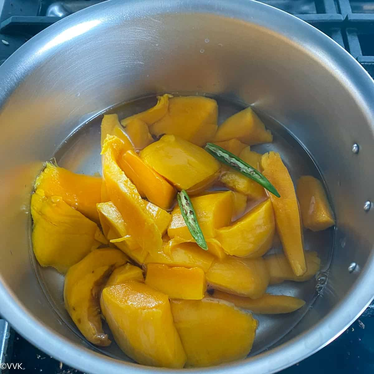 cooking the mangoes with green chili for the curry
