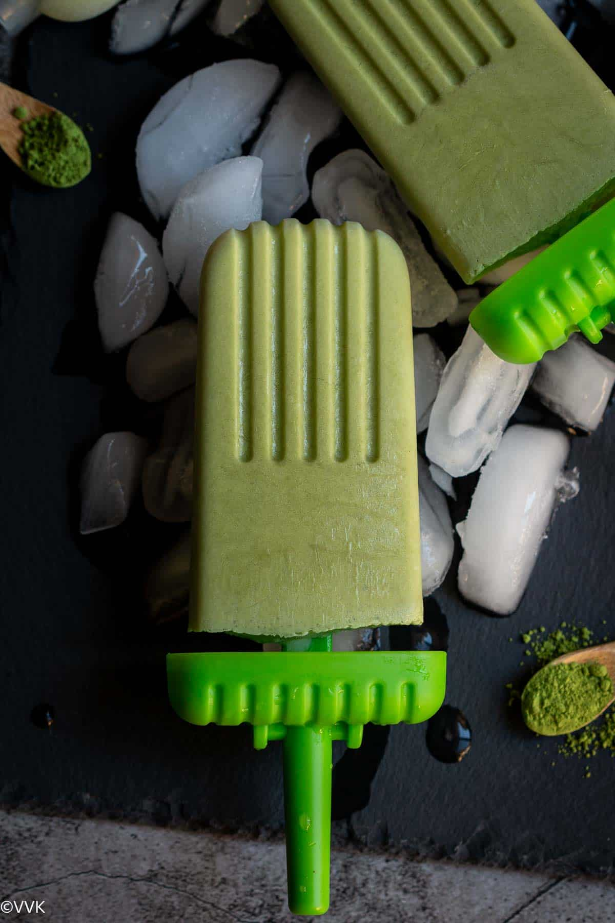 close up shot of matcha popsicle placed on ice cubes on a black slate board