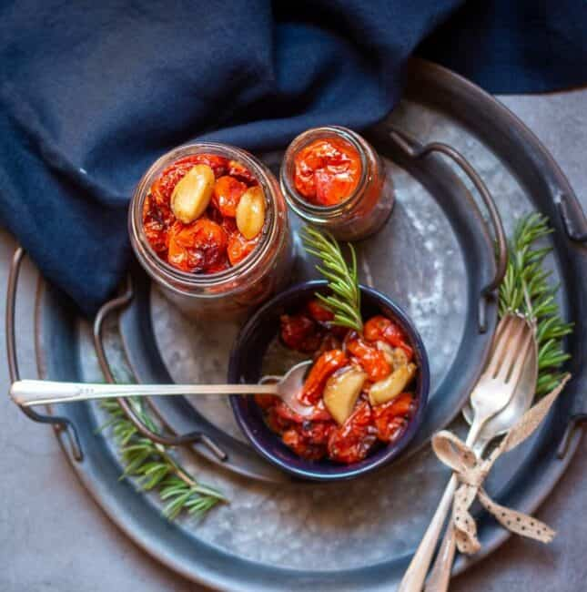 square image of roasted tomatoes in jars and black bowl