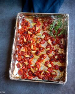 oven roasted tomatoes and garlic placed on baking tray