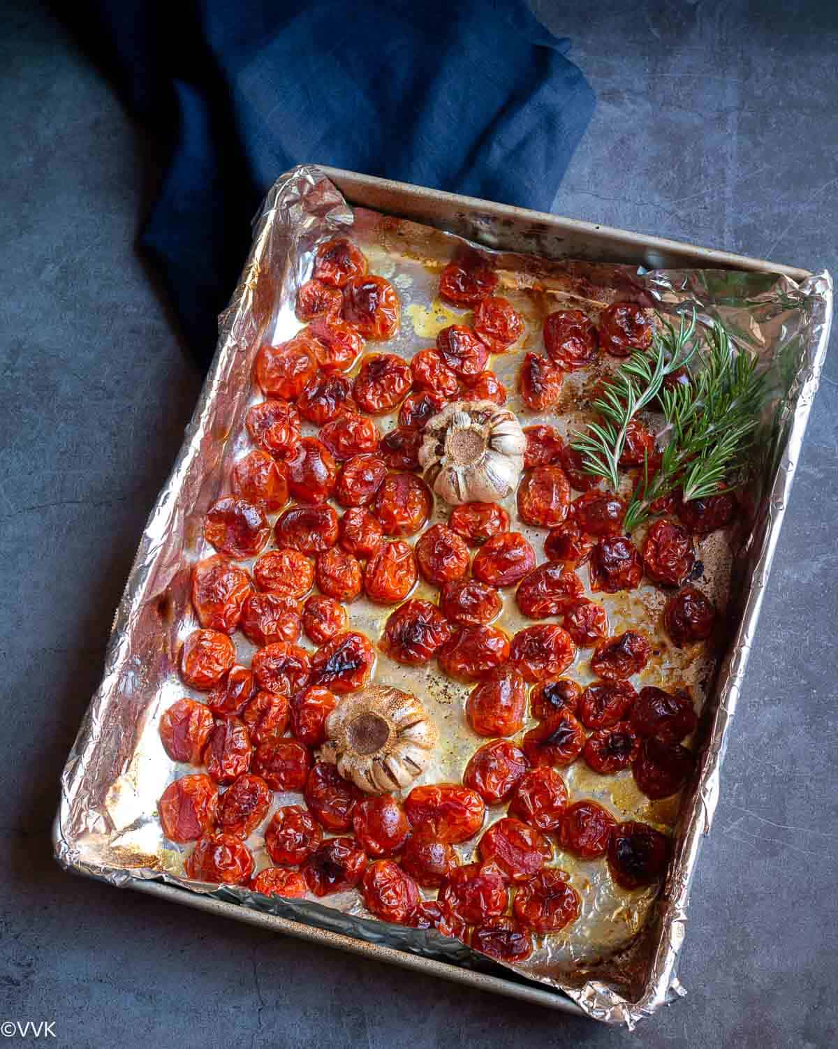 oven roasted tomatoes placed on baking tray with rosemary sprigs