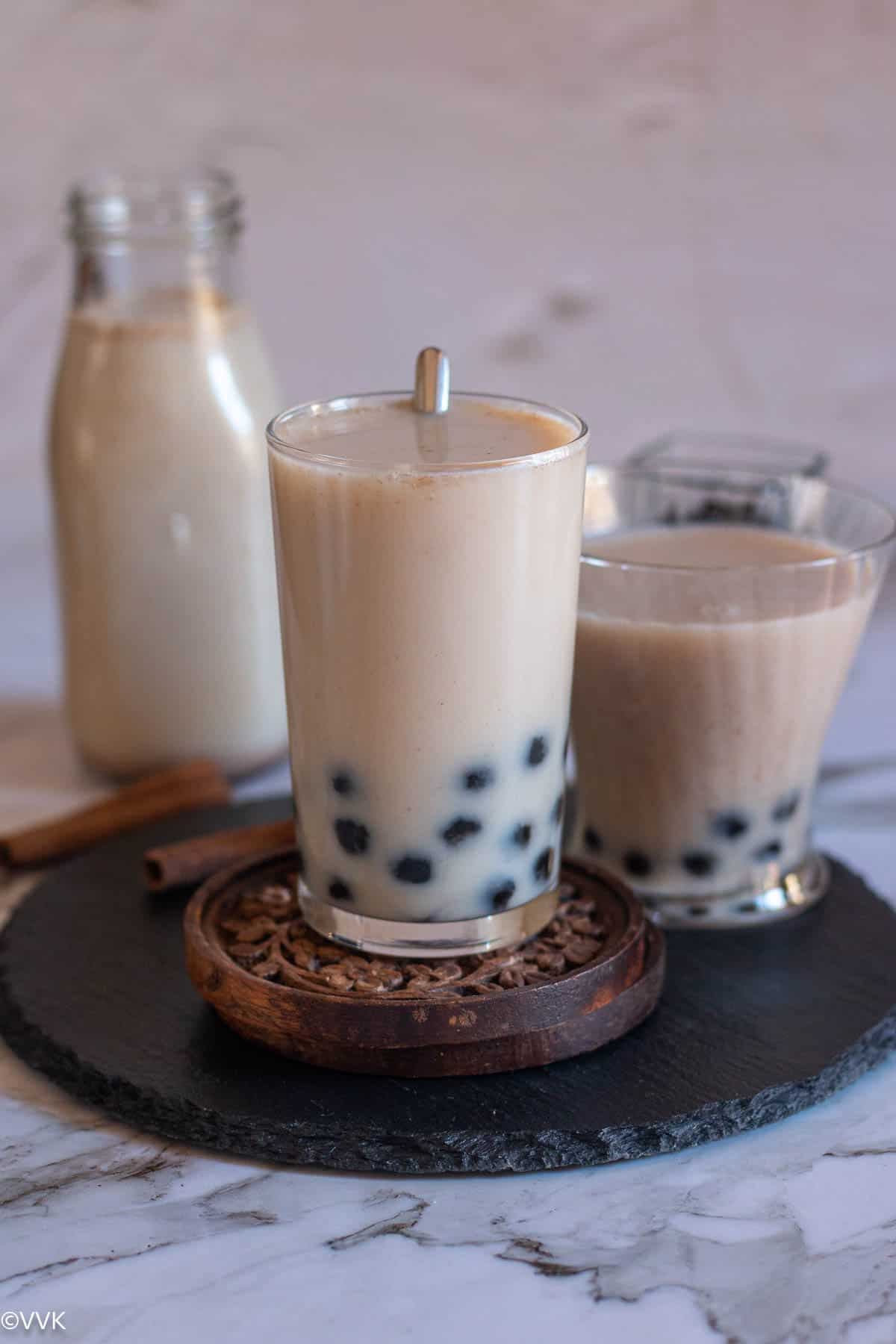 horchata served in tall glass with spoon inside placed on wooden coaster