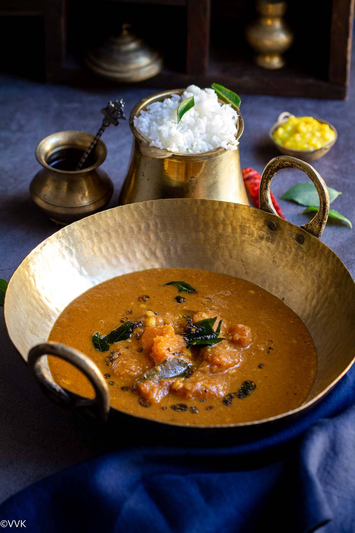 arachuvitta sambar served in a kadai with a side of rice, toor dal and ghee in a traditional set up