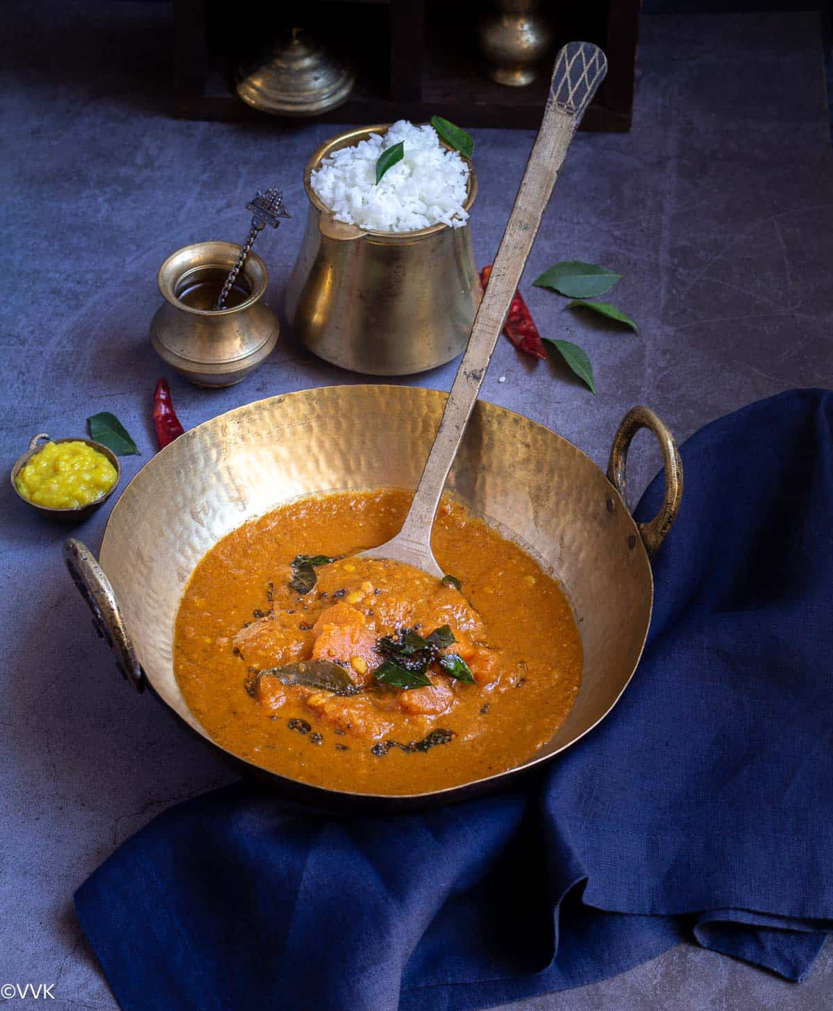 parangikai sambar served in a kadai with a ladle inside and with a side of rice, toor dal and ghee in a traditional set up