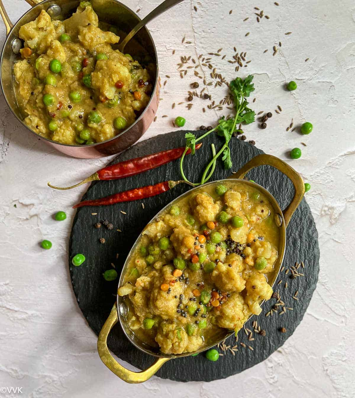cauliflower pattani poricha kootu served on two brass wares placed on black board with cumin seeds, red chilies and pepper on the side