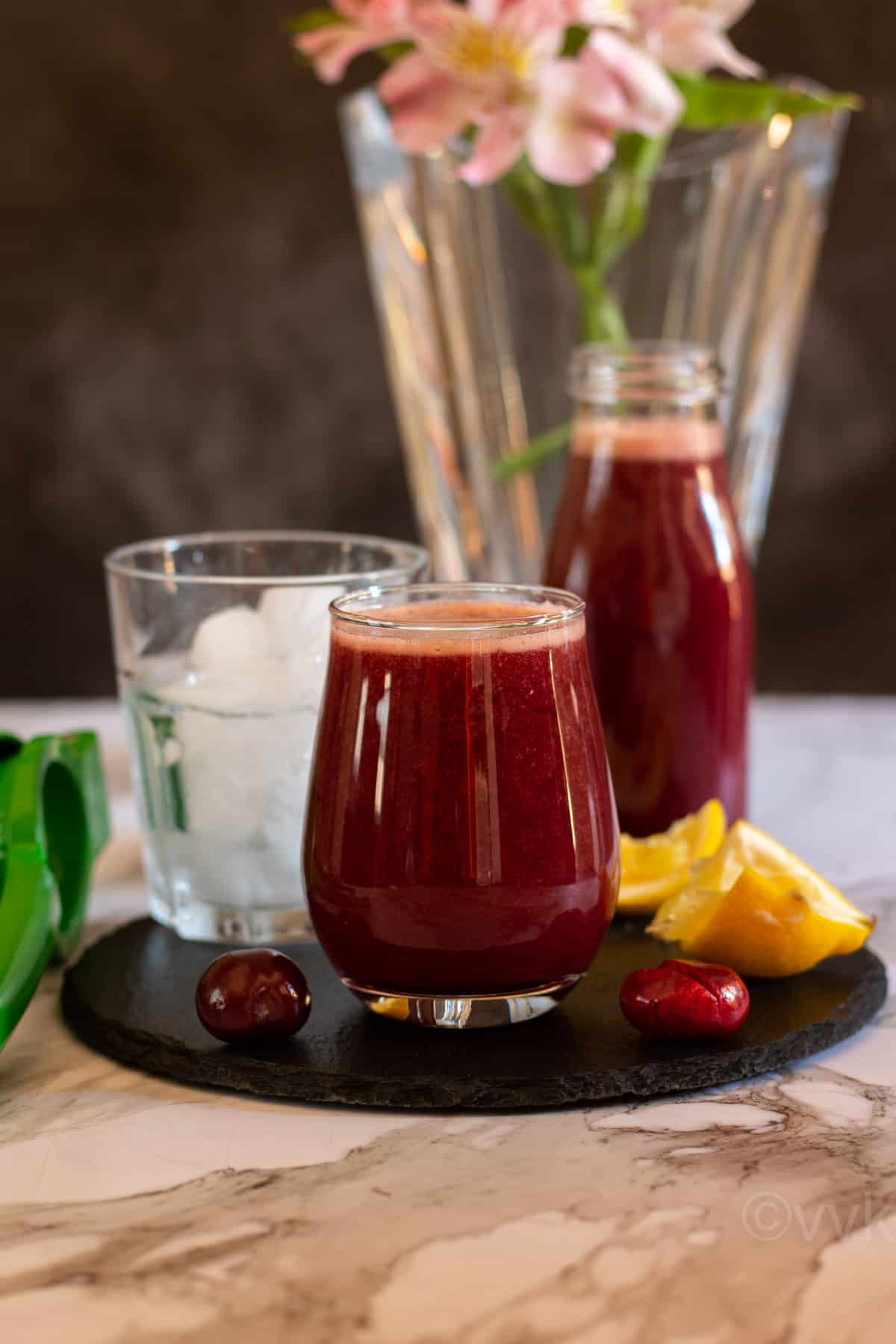homemade cherry juice with the syrup placed on a slate board with lemon wedges and cherries on the side