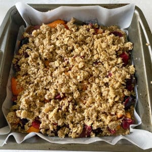 topping the fruit layer with oat flour crumb