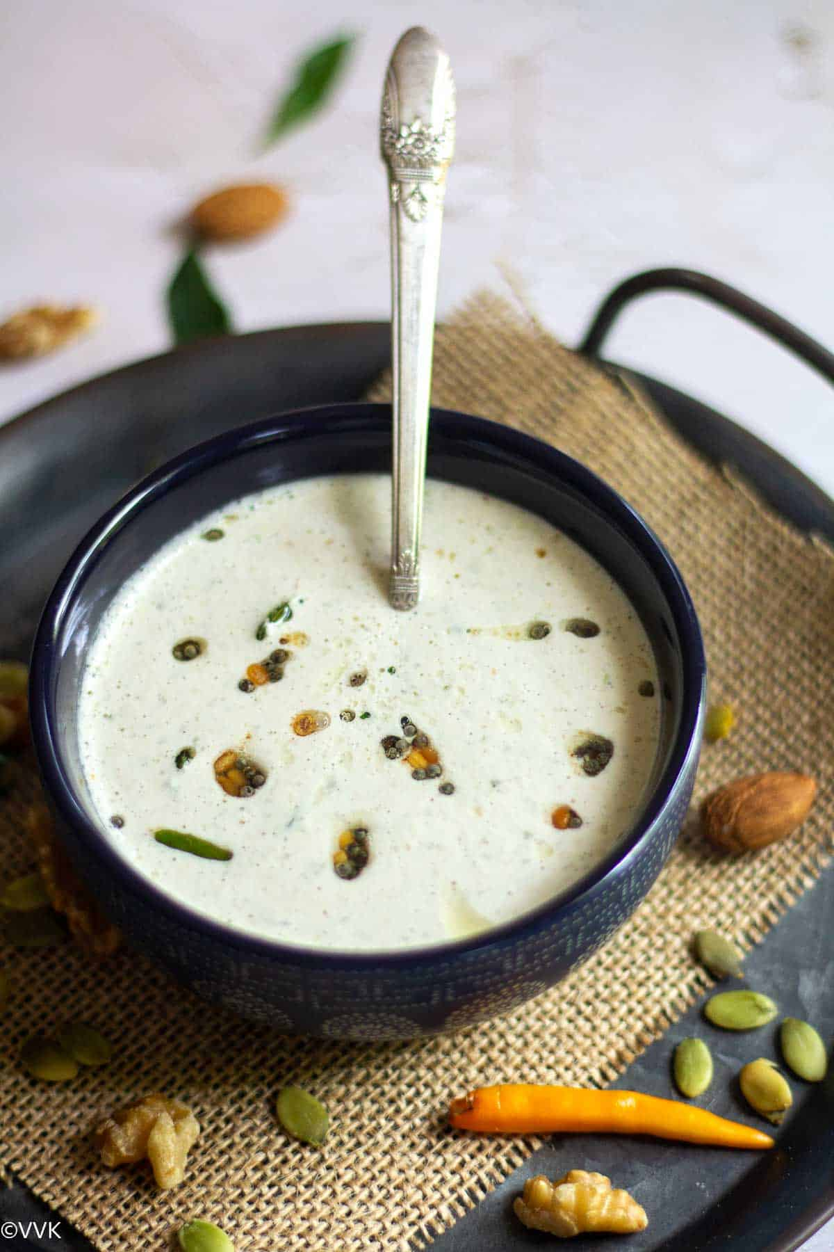 coconut chutney with nuts served in a bowl with a spoon inside placed on a burlap cloth with nuts on the side