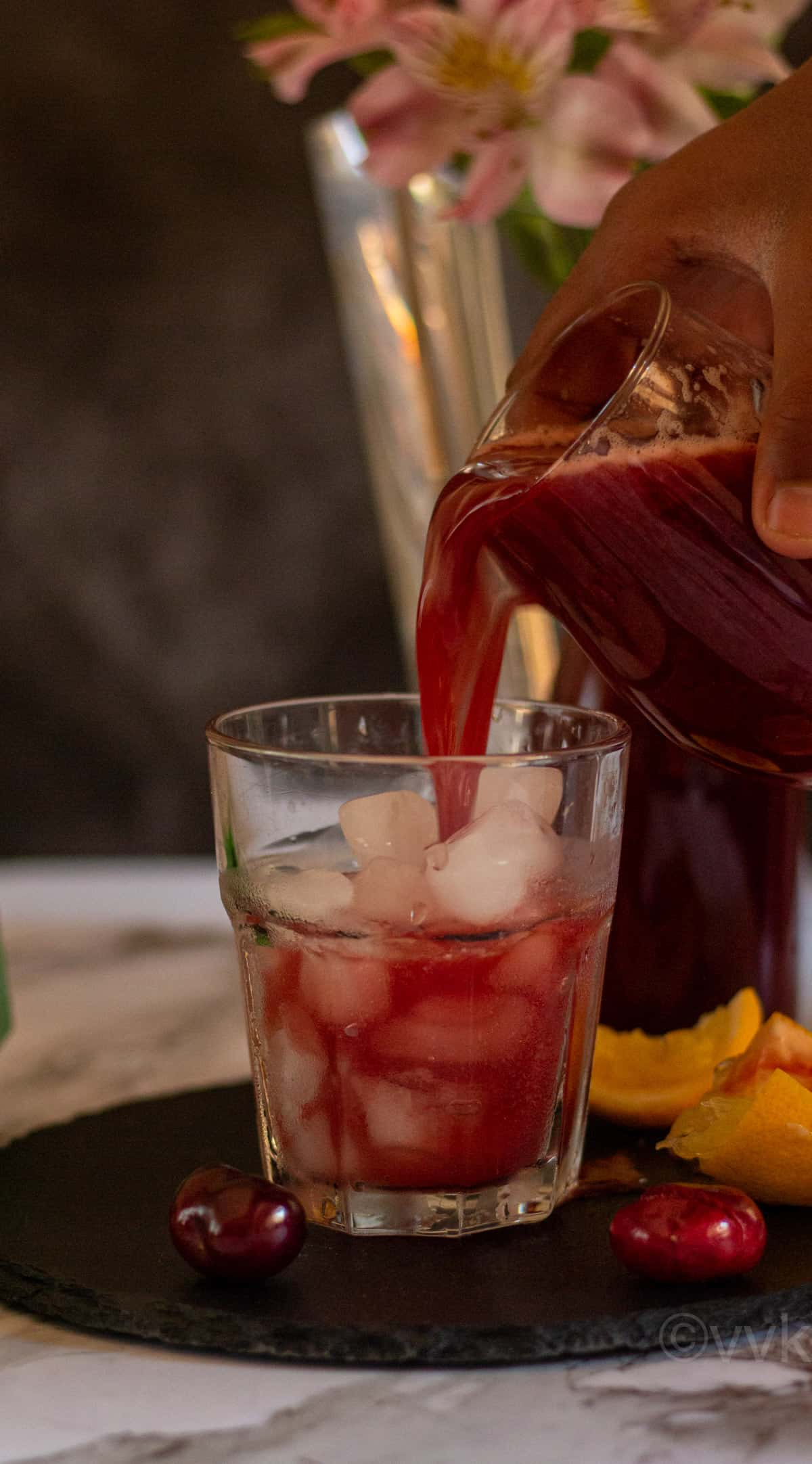 pouring shot of cherry lemonade into a glass filled with ice