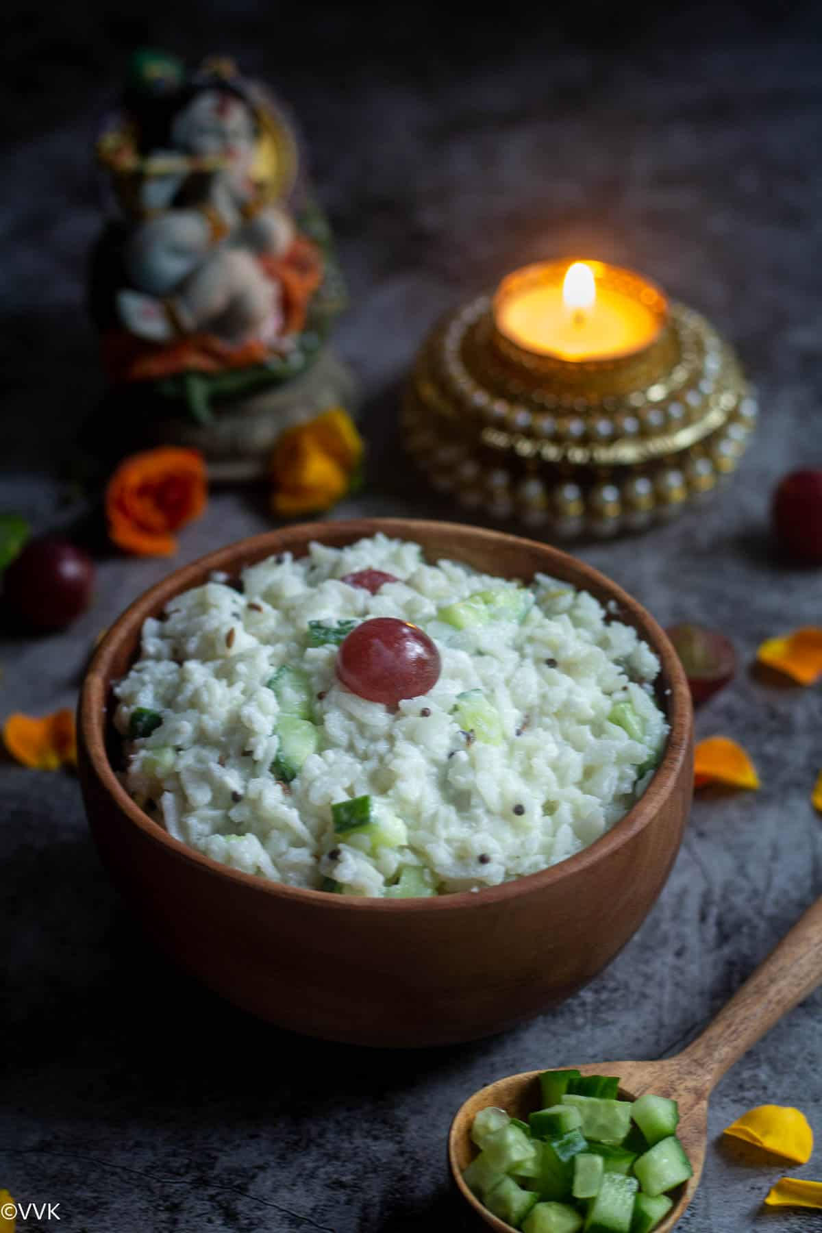 dahi poha served in wooden bowl with flower petals on the side and idol Krishna and candle on the top