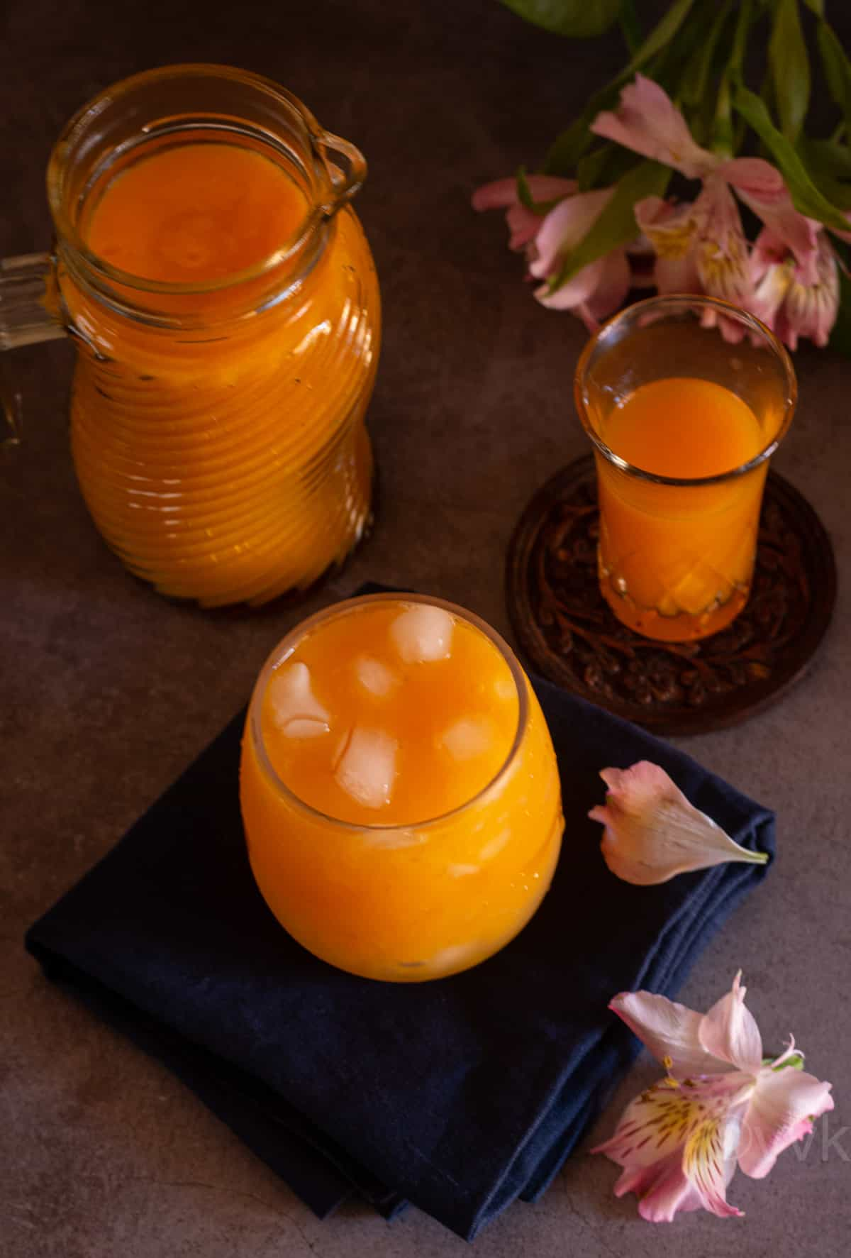 overhead angled shot of mango nectar with ice in a tall glass placed on blue napkin