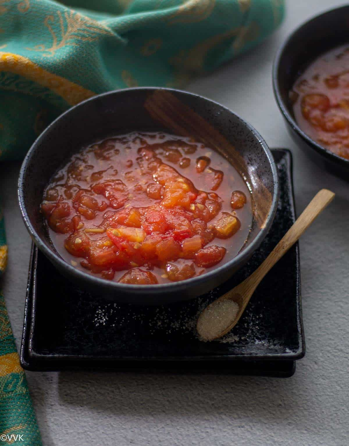 close up shot of tomato sweet pachadi served in black bowl with wooden spoon with sugar