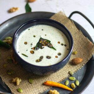 square image of nuts coconut chutney served in blue serveware placed on burlap cloth on a tray with nuts and chilies on the side