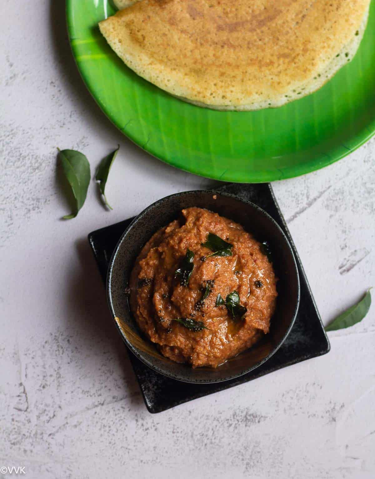 overhead shot of onion chutney topped with tempering with dosa behind