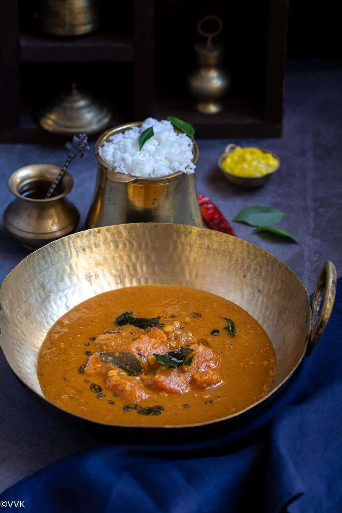 arasanikai sambar served in a kadai with a side of rice, toor dal and ghee in a traditional set up