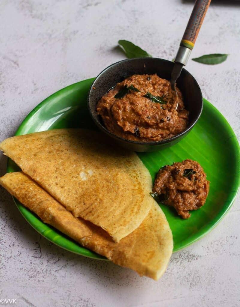 vengaya chutney with golden crispy dosa served on a leaf plate