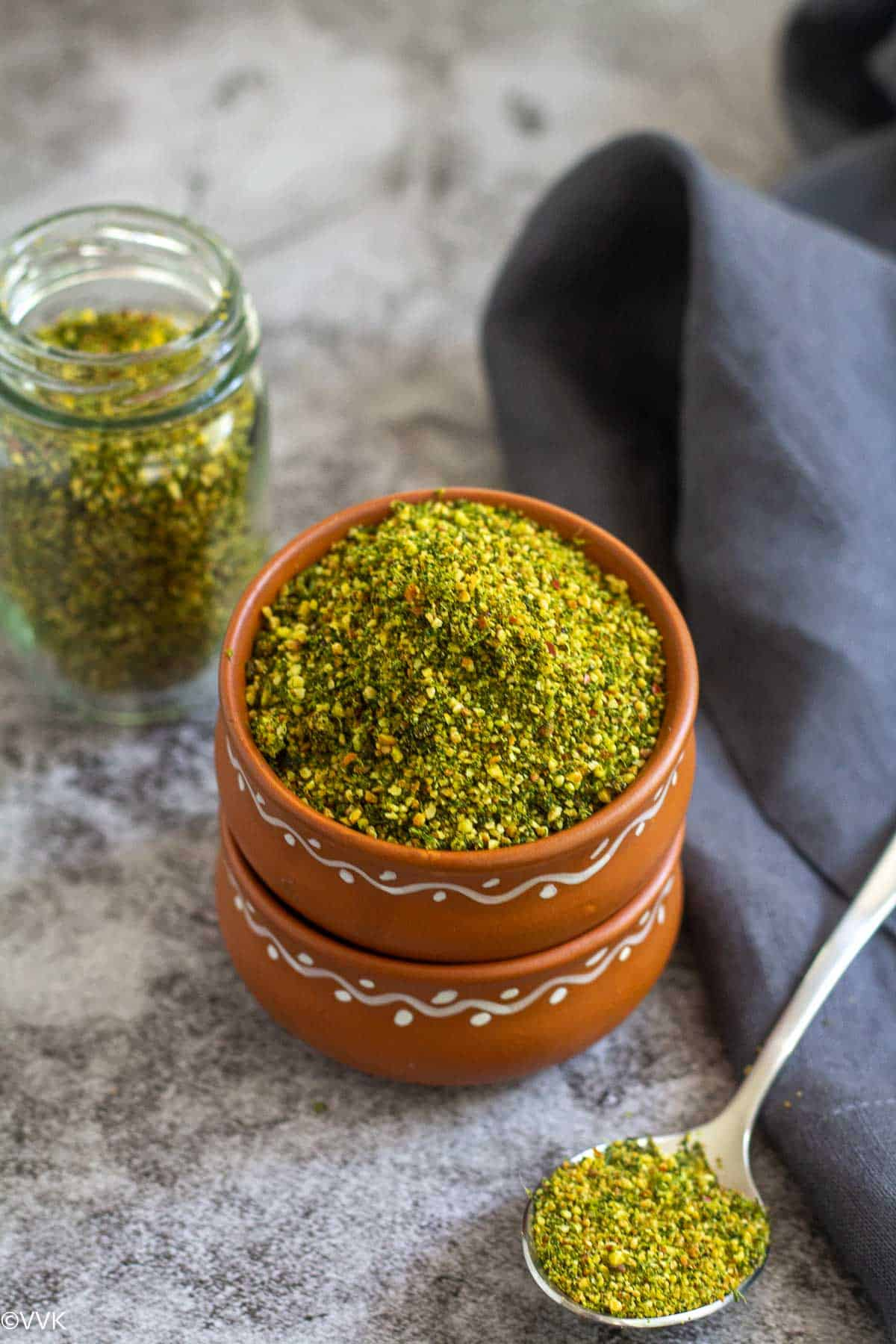 cilantro podi served in terracotta bowl and in a bottle on the side