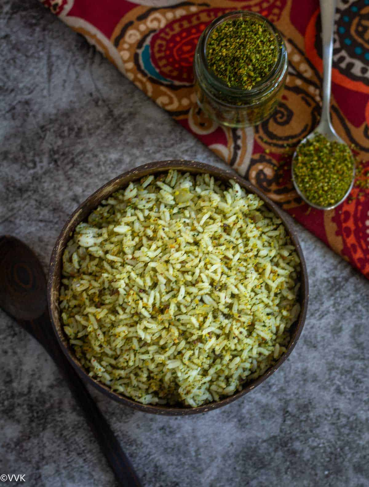 overhead shot of coriander rice in coconut bowl with podi on the side in the spoon