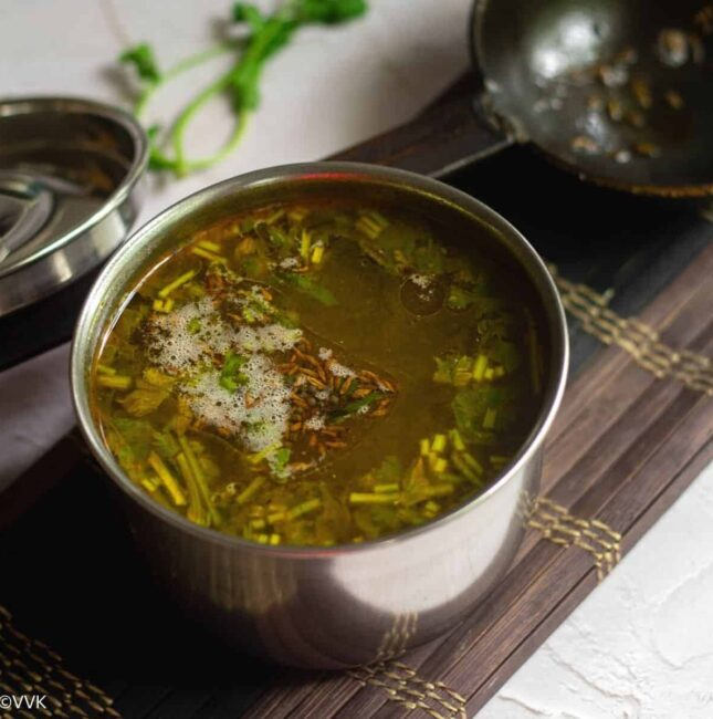 square image of rasam served in stainless vessel placed on a mat with a tempering spoon on the side