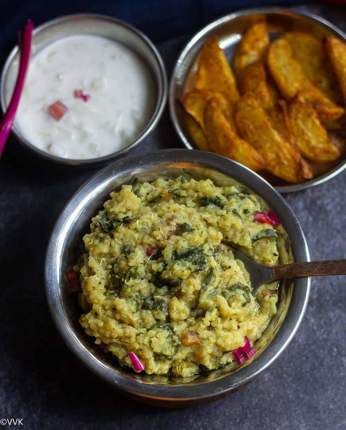 overhead shot of keerai sadam served with potato wedges and raita