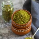 square image of cilantro podi served in terracotta bowl and in a bottle on the side