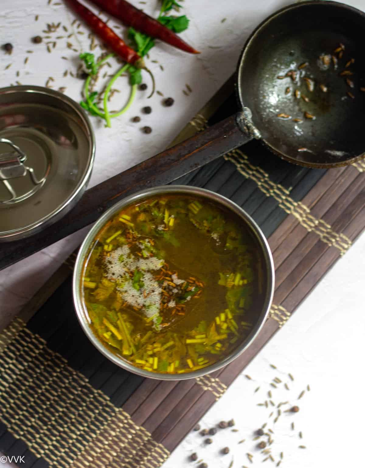 overhead shot of goddu rasam with spices on the side and tempering ladle on top