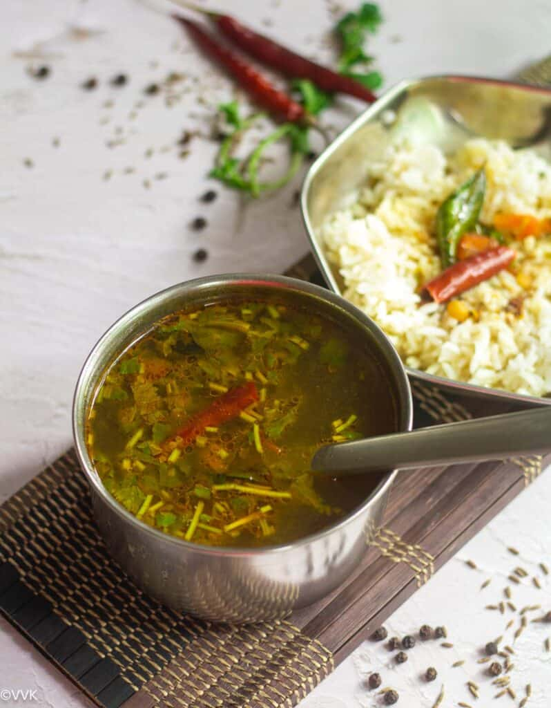 rasam with rice on the side. Rasam and rasam rice placed on a brown mat